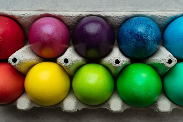 Kolorowe pisanki w tekturowym pudełku, widok zbliżenie strzał z góry