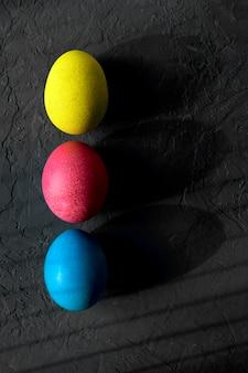 Kolorowe pisanki z głębokimi cieniami na czarnej ścianie, widok z góry. koncepcja wielkanocna