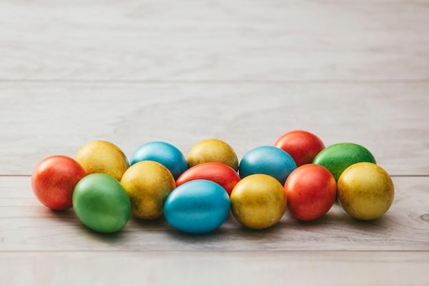 Kolorowe pisanki z masy perłowej na drewnianym stole na jasnym tle
