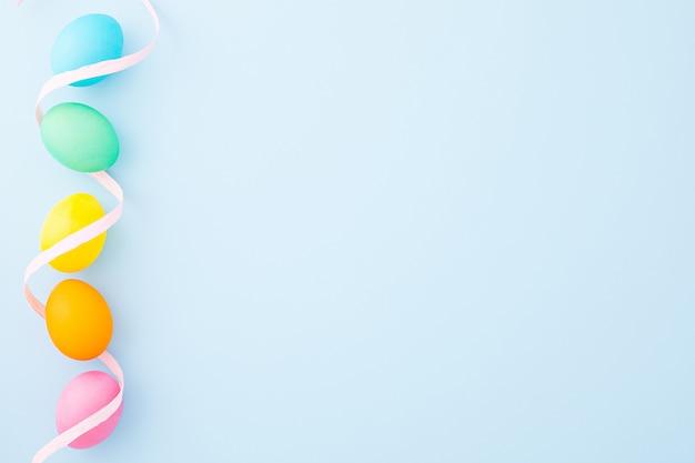 Kolorowe pisanki z różową wstążką na jasnoniebieskim tle. leżał płasko. widok z góry. skopiuj miejsce
