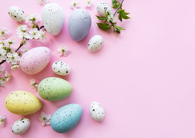 Kolorowe pisanki z wiosennymi kwiatami na różowym stole. granicy wakacje kolorowe jajko.