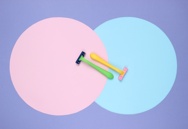 Kolorowe plastikowe brzytwy na fioletowym tle z różowymi, niebieskimi pastelowymi kółkami. minimalistyczne piękno martwa natura