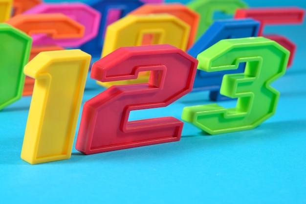 Kolorowe plastikowe cyfry 123 na niebieskim tle
