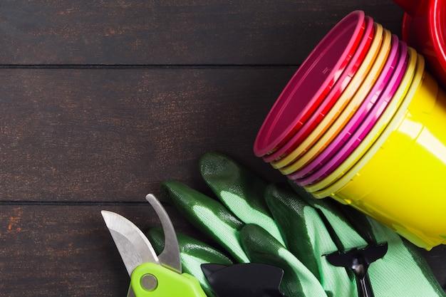 Kolorowe plastikowe doniczki, rękawiczki i narzędzia do ogrodnictwa i sadzonek