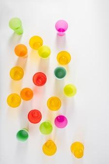 Kolorowe plastikowe kubki. szkodliwe jednorazowe plastikowe kubki stojące w rzędzie podczas sesji zdjęciowej w studio