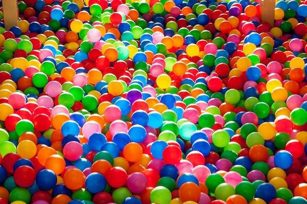 Kolorowe plastikowe kulki w basenie w pokoju gier. basen dla rozrywki z kolorowymi plastikowymi kulkami