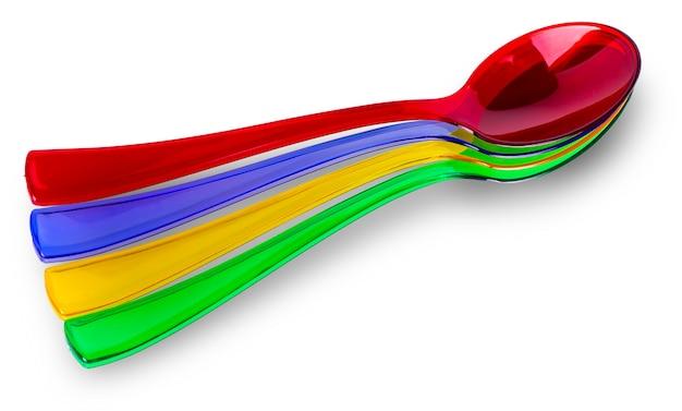 Kolorowe plastikowe łyżki na białym tle