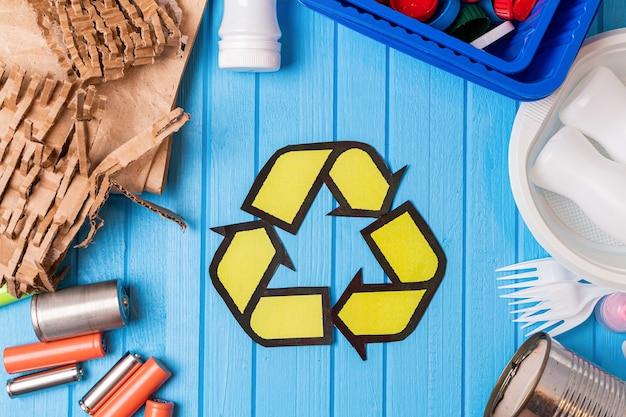 Kolorowe plastikowe, metalowe puszki, papier, karton, odpady z baterii i akumulatorów ze znakiem recyklingu na niebieskim tle