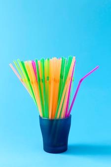 Kolorowe plastikowe słomki do picia w szklanym pojemniku na jasnoniebieskim tle