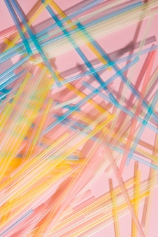 Kolorowe plastikowe słomki na różowym tle. zaopatrzenie eventowe i imprezowe. koncepcja zanieczyszczenia ziemi