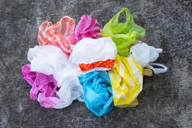 Kolorowe plastikowe torby na brudnej posadzce cementowej