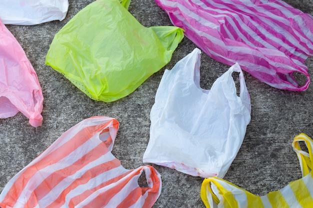 Kolorowe plastikowe torby na cementowej podłodze