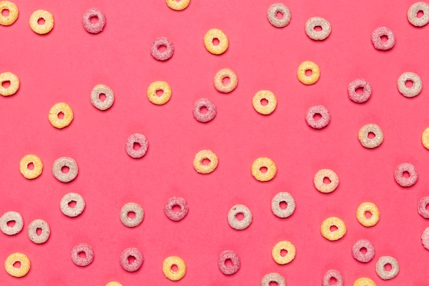 Kolorowe płatki zbożowe owoców pętle na różowym tle