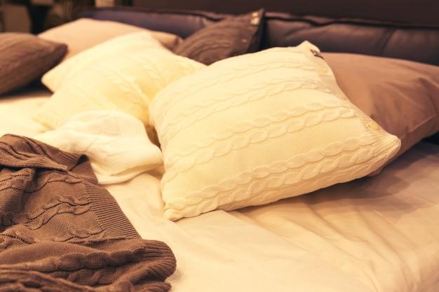 Kolorowe poduszki na łóżku hotelowym