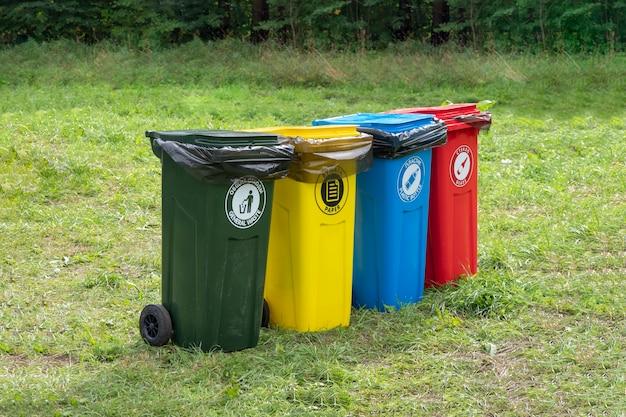 Kolorowe pojemniki do oddzielnej zbiórki śmieci na zielonym trawniku.