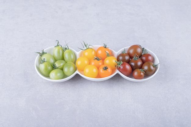Kolorowe pomidorki czereśniowe w białych miseczkach.