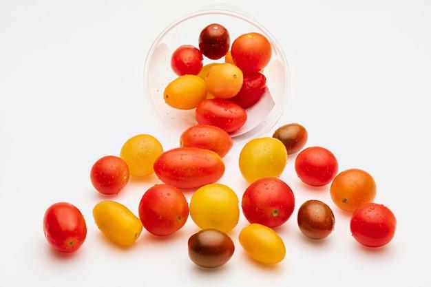 Kolorowe pomidory koktajlowe (czerwone, granatowe i żółte), świeże i surowe. w plastikowym słoiku. na białym tle