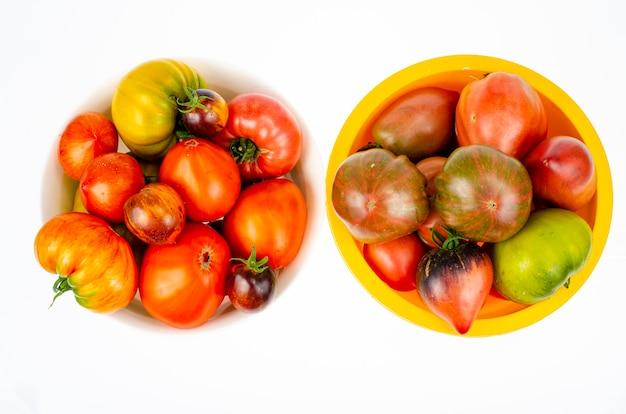 Kolorowe pomidory różnych odmian na białym tle. zdjęcie studyjne.