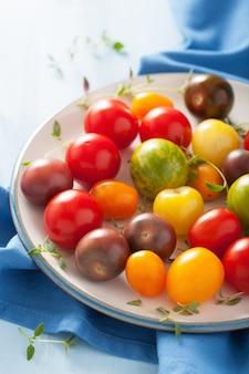 Kolorowe pomidory w talerzu na niebieskim szmatką