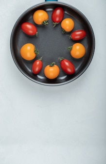 Kolorowe pomidory wewnątrz patelni na białym tle. wysokiej jakości zdjęcie