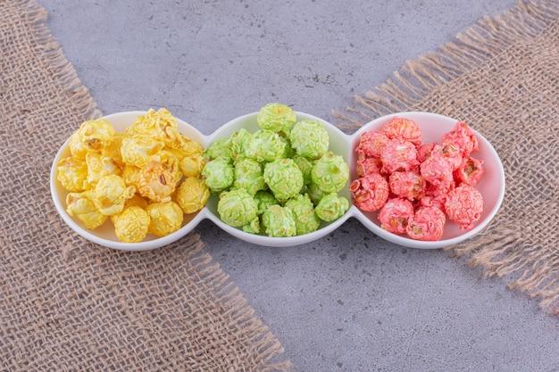 Kolorowe porcje cukierków popcornowych na potrójnym półmisku na marmurowym tle. zdjęcie wysokiej jakości