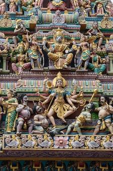 Kolorowe posągi hinduskich bóstw religijnych zdobiące wejście do świątyni hinduskiej w mieście little india, singapur. tło i tekstura jasnej architektury, z bliska