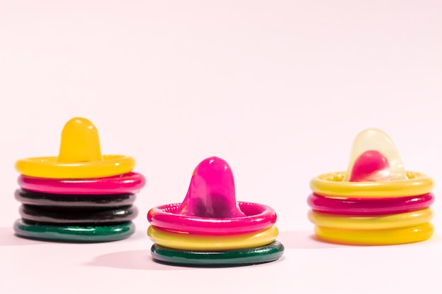 Kolorowe prezerwatywy na różowym tle