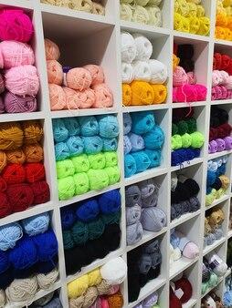Kolorowe przędze wełniane do dziania na półkach w koncepcji rękodzieła rękodzieła w sklepie pasmanteryjnym