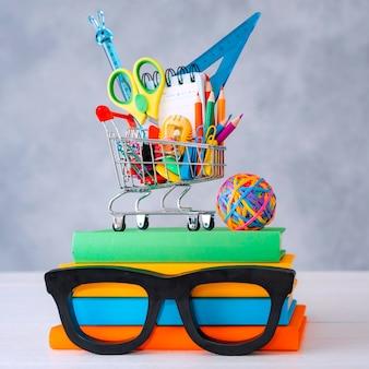 Kolorowe przybory szkolne kosz na zakupy szara ściana z miejscem na tekst kopii. stos książek z kolorowych okładek okulary ramki. koncepcja powrotu do szkoły na nowy rok akademicki.