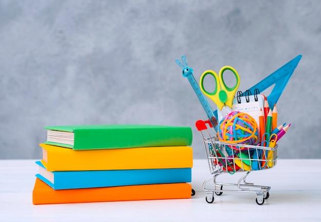 Kolorowe przybory szkolne w koszyku na zakupy na szaro z kopią miejsca na tekst.