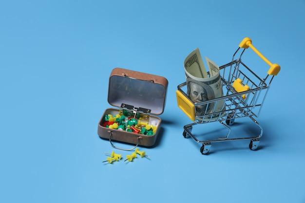 Kolorowe przyciski papeterii i wózek z pieniędzmi na niebiesko