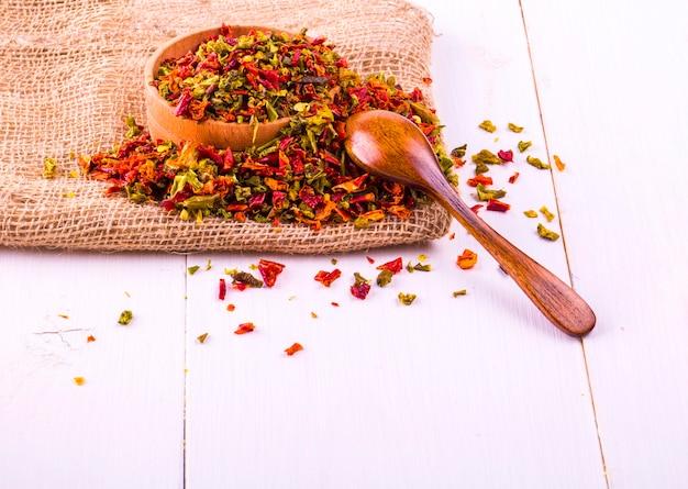 Kolorowe przyprawy z pieprzem w filiżance, sppon i juta na drewnianym stole