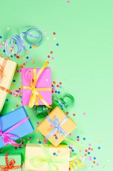 Kolorowe pudełka na prezenty, papierowe konfetti i kręcone serpentyny na zielonym tle