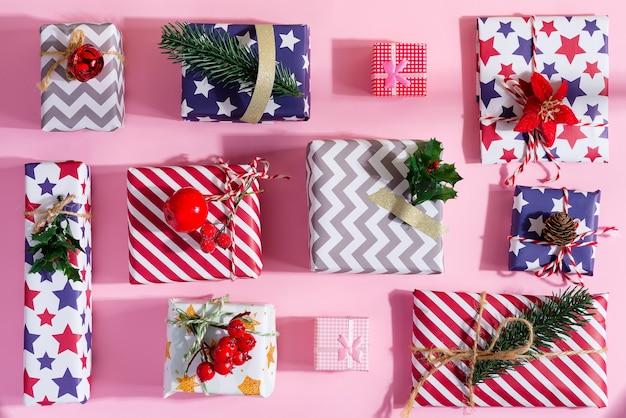 Kolorowe pudełka prezentowe z odświętną dekoracją na pastelowym różu. leżał na płasko.
