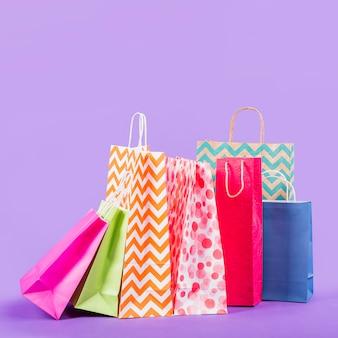 Kolorowe puste torby na zakupy na fioletowym tle