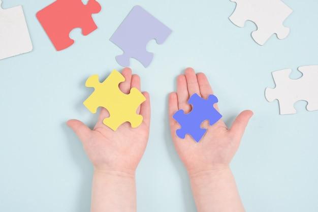 Kolorowe ręce dzieci trzymają puzzle na niebieskiej powierzchni