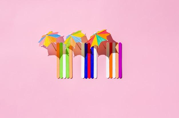 Kolorowe ręczniki plażowe z parasolami na różowym piasku plaży