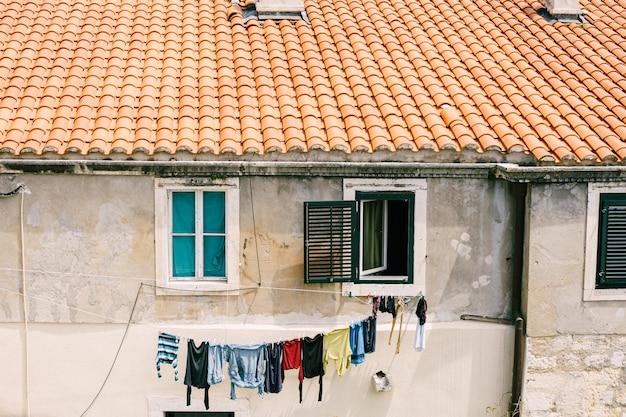Kolorowe ręczniki suszone są na sznurze między oknami na elewacji budynku