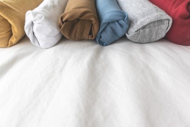 Kolorowe rolki t-shirt na białym łóżku koncepcja gotowa do podróży.