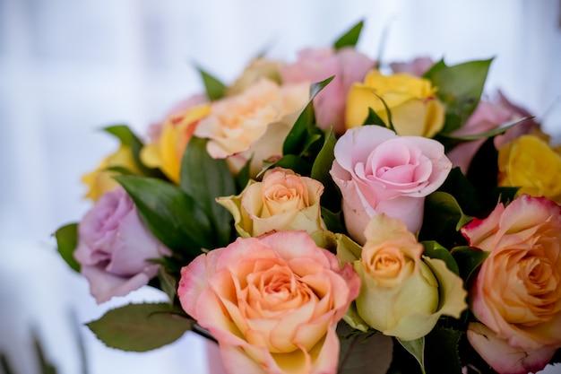 Kolorowe róże, piękny bukiet kwiatów. szczęśliwego dnia matki. mix róż w pudełku. stos różowych, żółtych, pomarańczowych, czerwonych i białych świeżych róż na białym tle. okrągły bukiet róż wielokolorowych