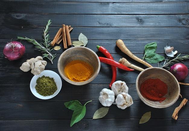 Kolorowe różne świeże, suszone zioła i przyprawy do gotowania na ciemnym tle