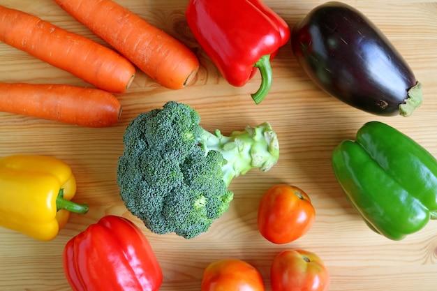 Kolorowe różne świeże warzywa rozrzucone na drewnianym tle