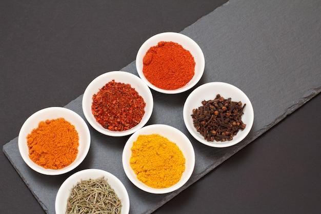 Kolorowe różne zmielone przyprawy, suche goździki i zioła w porcelanowych miskach na czarnej kamiennej desce do krojenia. widok z góry.