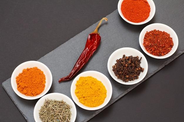Kolorowe różne zmielone przyprawy, szafran, kminek, curry, suchy rozmaryn i goździki w porcelanowych miseczkach na czarnej kamiennej desce do krojenia z suszoną czerwoną papryką. widok z góry.