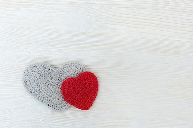 Kolorowe serca z dzianiny na białym drewnie.