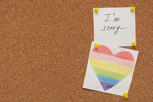 Kolorowe serce i przykro mi napis napis na białym papierze wyciśniętym na tablicy korkowej