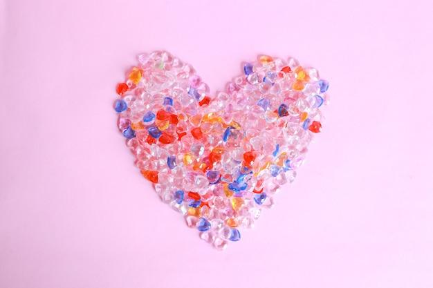 Kolorowe serce z kulek na różowym tle