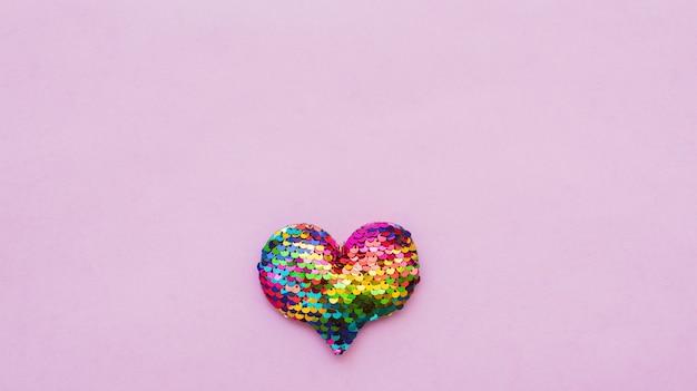 Kolorowe serduszko wykonane z cekinów na różowym tle. skopiuj miejsce