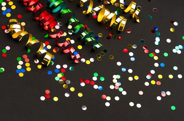 Kolorowe serpentyny i konfetti na tle czarnego papieru. dekoracja imprezowa