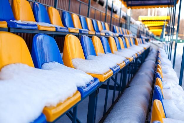 Kolorowe siedzenia pokryte śniegiem w zimowym śnieżnym stadionie.